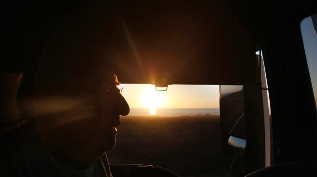 Semi truck driver with a sunset
